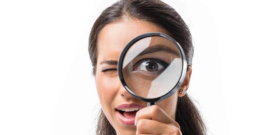 Female Using Magnifying Glass - Banner image for Spotting the Leak Blog
